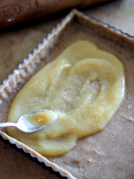un peu de compote sous les pommes sur la pâte sablée à la cannelle