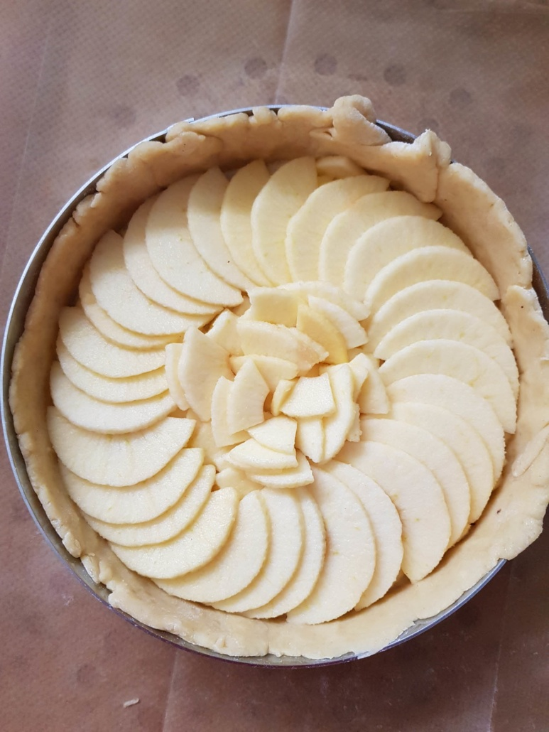 neatly arrange slices of apple on the tart